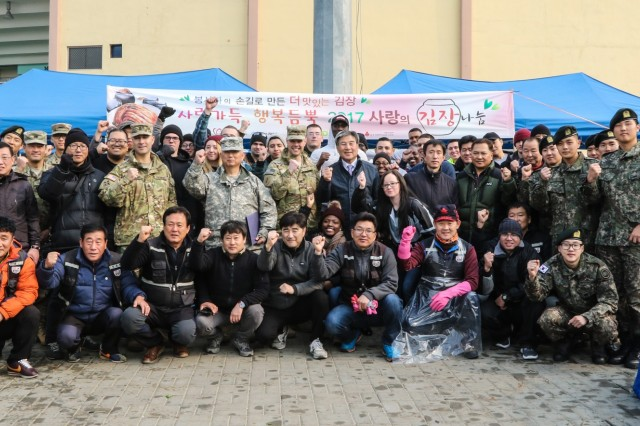 Soldiers assigned to 210th Field Artillery Brigade, 2nd Infantry Division/ROK-US Combined Division and 125th Mechanized Infantry Battalion, Republic of Korea Army 26th Mechanized Infantry Division take a group photo with people from local community organizations during the 2017 Dongducheon Volunteer Center Annual Kimchi Charity Event at Dongducheon Multi Complex Stadium, Dongducheon, Republic of Korea, Nov. 22, 2017. At the event, they made Kimchi and distributed them to seniors who were in need. (U.S. Army Photo by Sgt. Michelle U. Blesam, 210th FA Bde Public Affairs)