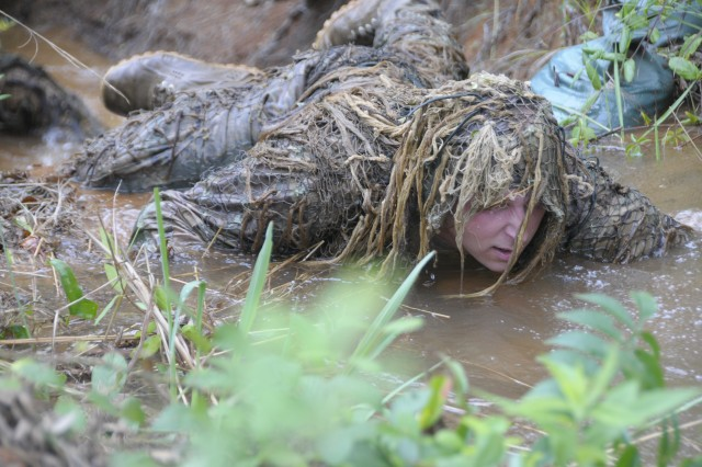 Students are taught camouflage and concealment techniques at the U.S. Army Sniper School at Fort Benning, Georgia. They learned to weather a ghillie suit by crawling through ditches filled with water, mud, rocks, vegetation and fallen tree branches.