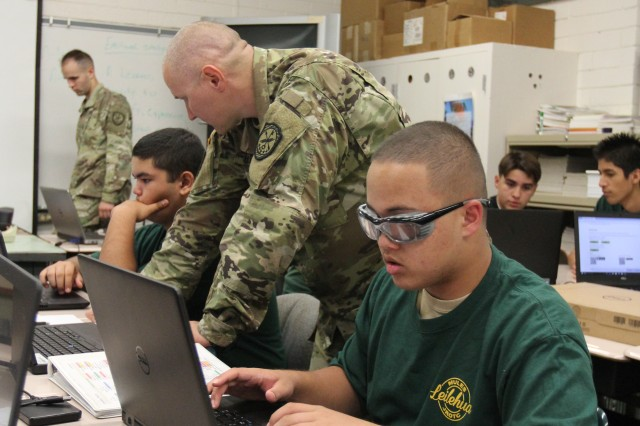 WAHIAWA, Hawaii -- Chief Warrant Officer 3 (CW3) Lee Unrein, Detachment Hawaii, 782nd Military Intelligence (MI) Battalion, based out of Schofield Barracks, teaches Windows operating system basics and security to Leilehua High School JROTC students Daniel Brink (right) and Nicholas Lipka.