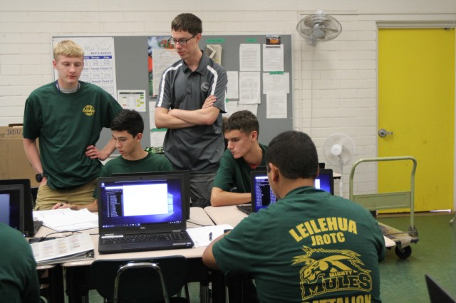 WAHIAWA, Hawaii -- Spc. Jacob Cochran (standing right), Detachment Hawaii, 782nd Military Intelligence (MI) Battalion, based out of Schofield Barracks, teaches Leilehua High School JROTC cadets (left to right) McCain Compton, Christian Villarreal, and Tyler McWilliams, about the Linux operating system, Nov. 20.