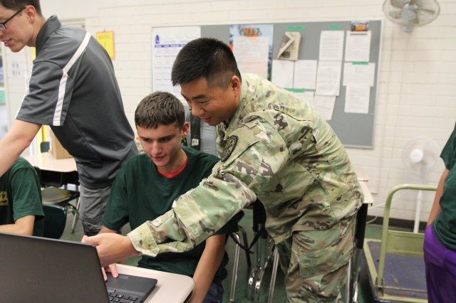 WAHIAWA, Hawaii -- Sgt. Kevin Kang, Detachment Hawaii, 782nd Military Intelligence (MI) Battalion, based out of Schofield Barracks, talks to Leilehua High School JROTC cadet Tyler McWilliams about the Linux operating system, Nov. 20.