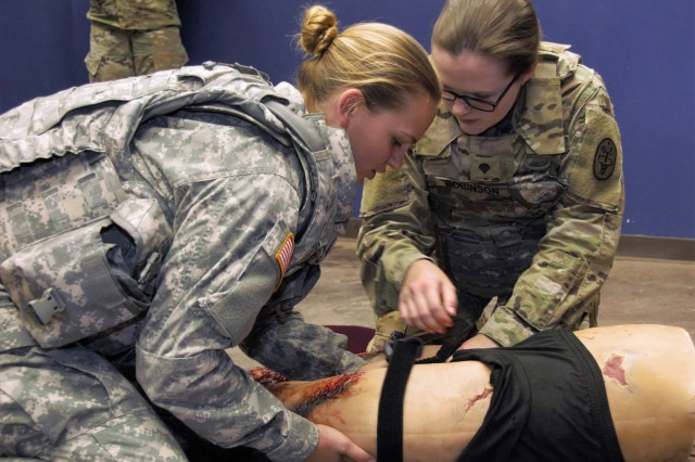 (From left) Spcs. Alyssa Hobbs and Breana Robinson, both combat medics at William Beaumont Army Medical Center's Inpatient Surgical Unit, apply a tourniquet to a simulated casualty during Tactical Combat Casualty Care training at the Medical Simulation Training Center at Fort Bliss, Nov. 16.