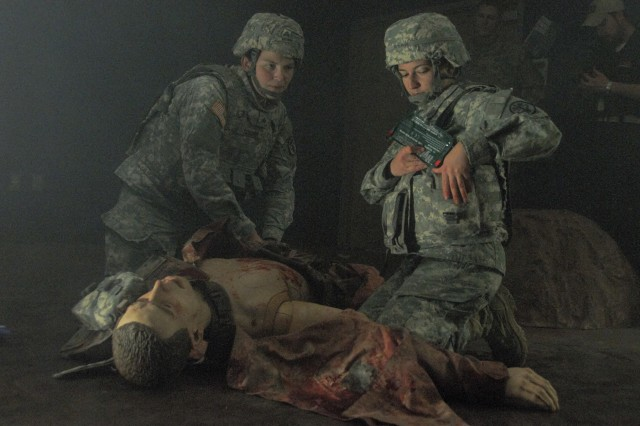 (From left) Sgt. Deborah Schumm, combat medic, Inpatient Surgical Unit, William Beaumont Army Medical Center and 1st Lt. Kate Abbott, Registered Nurse, Inpatient Surgical Unit, WBAMC, assess and prepare a simulated casualty for treatment during Tactical Combat Casualty Care training at the Medical Simulation Training Center at Fort Bliss, Nov. 16.