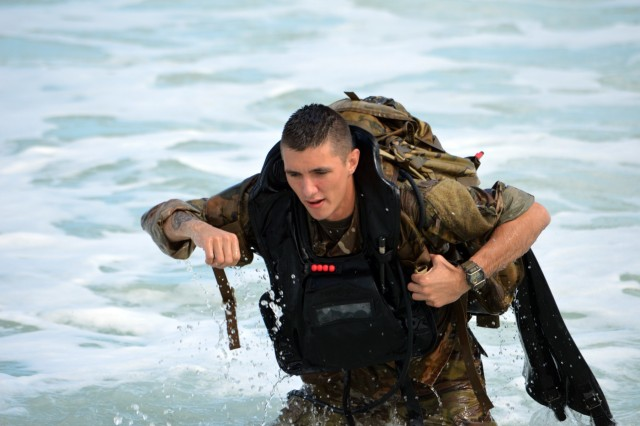 A scout swimmer assigned to the 3rd Squadron, 4th Cavalry Regiment, 3rd Brigade Combat Team, 25th Infantry Division, lifts his gear after swimming a kilometer to the beach at Marine Corps Training Area Bellows, Hawaii, on Nov. 29, 2017. The Soldiers participated in waterborne training with his unit in the Pacific Ocean. (U.S. Army photo by Staff Sgt. Armando R. Limon, 3rd Brigade Combat Team, 25th Infantry Division)