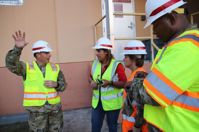 Sharon Garay Rodriguez, Brig. Gen. Diane Holland, and Master Sgt. Lavander Talley (center to right) listen as Col. John Lloyd, commander of the Task Force Power Restoration mission, provides an update on the installation of 50-megawatt generators at Palo Seco Power Plant in San Juan.