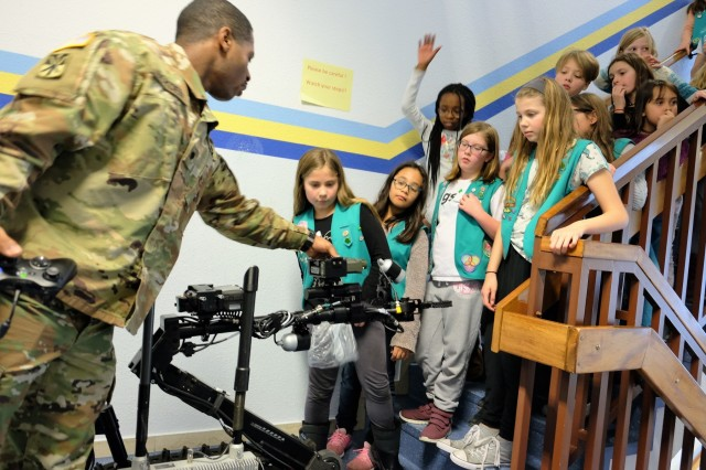 Spc. Jonathan Boyden, 773rd Civil Support Team, demonstrates the Talon IV surveying robot to the Sembach Girl Scouts Juniors Troop 991 Monday, Dec. 4, 2017 at Sembach Middle School. The Juniors were earning the robotics patch, and the 773rd CST brought the robot for the meeting.