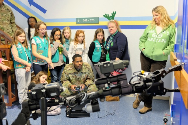 Spc. Jonathan Boyden, 773rd Civil Support Team, shows Sembach Girl Scouts Juniors Troop 991 how the Talon IV surveying robot can open a door Monday, Dec. 4, 2017 at Sembach Middle School. The Juniors were earning the robotics patch, and the 773rd CST brought the robot for the meeting.