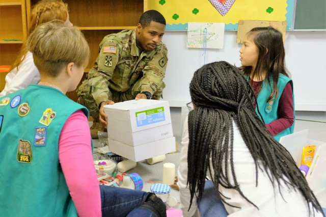 Spc. Jonathan Boyden, 773rd Civil Support Team, builds a robot with girls from Sembach Girl Scouts Juniors Troop 991 Monday, Dec. 4, 2017 at Sembach Middle School.