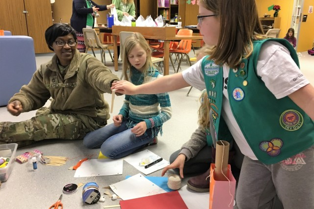 Sgt. 1st Class Yuolanda Carey, 773rd Civil Support Team survey team chief, builds a robot with girls from Sembach Girl Scouts Juniors Troop 991 Monday, Dec. 4, 2017 at Sembach Middle School.