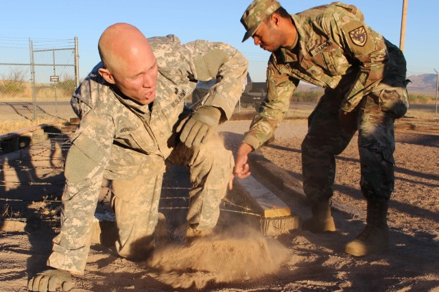 Staff Sgt. James Russell, who won Platoon Sergeant of the Quarter, from the 305th Military Intelligence Bn., completes the low crawl portion of the obstacle course during the 111th Military Intelligence Brigade Platoon Sergeant, Noncommissioned Officer (NCO), and Soldier of the Quarter competition at Fort Huachuca 14 Nov