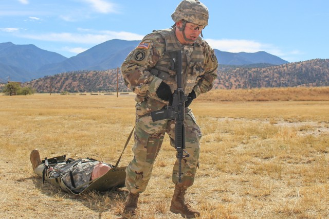 Staff Sgt. William Smithe, who won NCO of the Quarter, from the 344th Military Intelligence Bn. located at Goodfellow Air Force Base in Texas, executes an evacuation of a casualty prior to his stress shoot during the 111th Military Intelligence Brigade Platoon Sergeant, Noncommissioned Officer (NCO), and Soldier of the Quarter competition at Fort Huachuca 15 Nov.