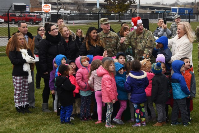 Maj. Gen. LeMasters and his helpers push the plunger to light the holiday tank.