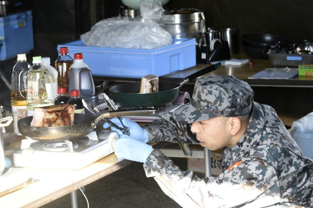 20171204-N-QY397-055 CAMP SENDAI, Japan -- An airman assigned to the Japan Air Self-Defense Force (JASDF), Team Matsushima, finalizes plating during Iron Chef 2017 during exercise Yama Sakura 73. Four teams comprised of American and Japanese forces participated in a friendly cooking competition during the exercise. Yama Sakura is an annual bilateral command post exercise involving the U.S. Military and the Japan Ground Self-Defense Force (JGSDF).The purpose of the exercise is to enhance U.S. and Japanese combat readiness and interoperability while strengthening bilateral relationships and demonstrating U.S. resolve to support the security interests of allies and partners in the Indo-Asia-Pacific region. During the exercise, U.S. military members and JGSDF members exchange ideas, tactics, techniques, military experiences, and culture. (U.S. Navy Photo by MC2 (SW) Whitehead, Marquis)