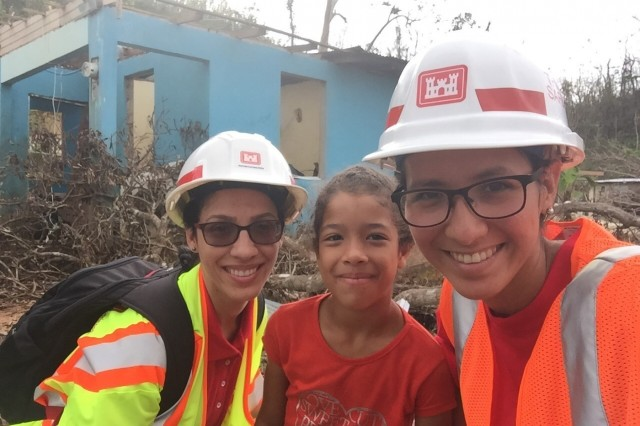 Marielys Ramos-Villanueva, a research civil engineer in the Coastal Hydraulic Laboratory, is one of twenty University of Puerto Rico at Mayagüez alumni working as part of recovery efforts in Puerto Rico. Ramos-Villanueva, left, is lead for the northern and central areas of Operation Blue Roof.  She and another U.S. Army Corps of Engineers employee, Cynthia Rodriquez, are visiting Victoria's house to order the installation of the protective tarp so Victoria and her family can leave the shelter and return to their home.