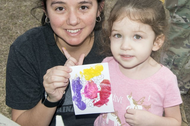 Rebecca Eller, wife of Capt. Mike Eller, a student at the Adjutant General School, and her 3-year-old daughter Isabella, hold up artwork the youngster created at an arts and crafts booth at the event.