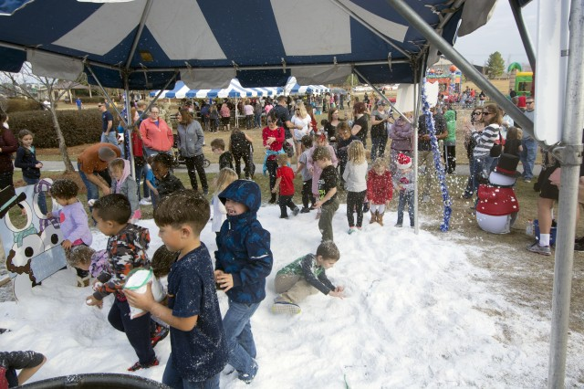 Fort Jackson children play in the snow during the Fort Jackson Winter Wonderland Christmas Tree Lighting celebration Dec. 1 at Patriot Park near the Solomon Center on post. Attendees were awarded with games, food, and even snow to play in before the tree was lit and Santa arrived via Fort Jackson fire truck.
