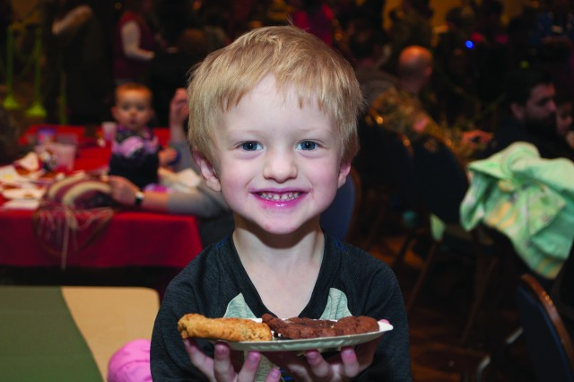 Three-year-old Shane Haake enjoys a treat during a holiday celebration held Dec. 4 at the Commons, Fort Drum, N.Y..