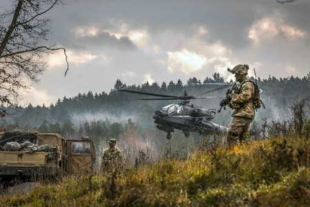 An AH-64 Apache attack helicopter takes off near Soldiers participating in the Allied Spirit VII training exercise, Nov. 18, 2017 at Grafenwoehr, Germany. The U.S. Army, along with its allies and partners, continues to forge a dynamic presence with a powerful land network that simultaneously deters aggression and assures the security of the region.