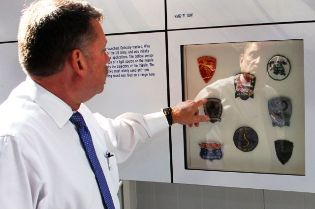 Bob Mitchell, curator at the U.S. Army Aviation Museum, points out the recurring themes in unit patches on display at the museum.
