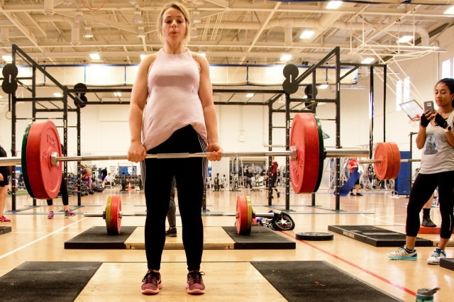 Moriah Harmon, military spouse, performs a deadlift while her workout partner, Denae Barajas, military spouse, records the movement.