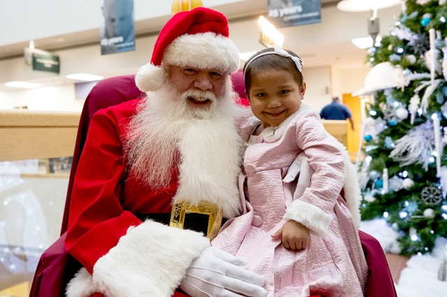 "5-year-old Lourdes Esther ""LE"" Torres spends some quality time with Santa following a ceremony at Madigan Army Medical Center where she helped the commander light the Christmas tree and menorah on Dec. 1 at Joint Base Lewis-McChord, Wash."