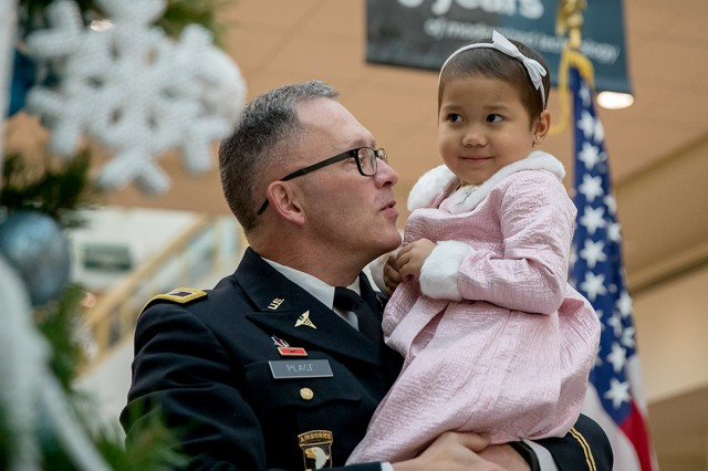 "Madigan Army Medical Center Commander Col. Michael L. Place and 5-year-old Lourdes Esther ""LE"" Torres have a look at the Christmas tree before lighting it and a menorah at a ceremony Dec. 1 on Joint Base Lewis-McChord, Wash."