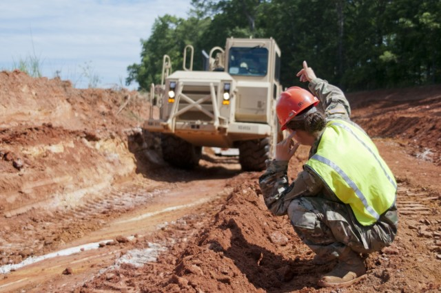 Army Staff Sgt. Valarie Mitchell, a heavy equipment operator assigned to the 725th Engineer Support Platoon, 105th Engineer Battalion, 130th Maneuver Enhancement Brigade, ground guides a Soldier driving a wheeled-tractor scrapper during a parking lot expansion project at the Western North Carolina Agriculture Center in Fletcher, North Carolina, June 14, 2017. The project was a joint partnership between the North Carolina National Guard and the North Carolina Department of Agriculture and Consumer Services. (U.S. Army National Guard photo by Staff Sgt. Mary Junell, 382nd Public Affairs Detachment/Released)