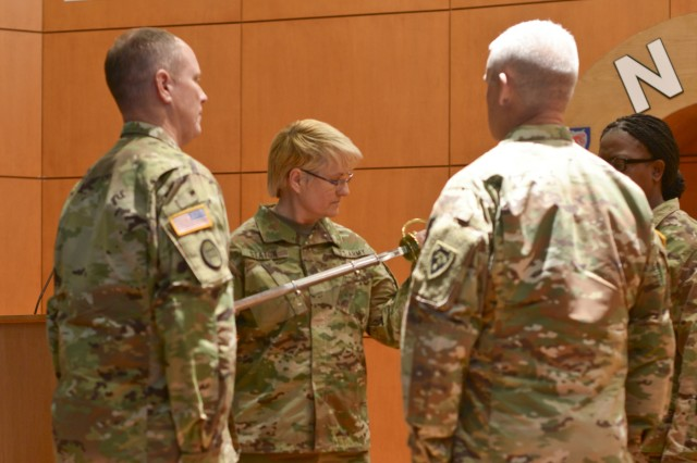 Command Sgt. Maj. Diana Staton, the incoming senior enlisted leader (SEL) for 60th Troop Command, inspects a noncommissioned officer sword after it was handed to her during a change of responsibility ceremony at North Carolina National Guard's Joint Force Headquarters in Raleigh, North Carolina, Dec. 2, 2017. The passing of the sword from the outgoing SEL to the commander and then to the incoming SEL signifies the passing of responsibility of the organization's Soldiers from the previous enlisted leader to the incoming. (U.S. Army National Guard photo by Staff Sgt. Mary Junell, 382nd Public Affairs Detachment/Released)