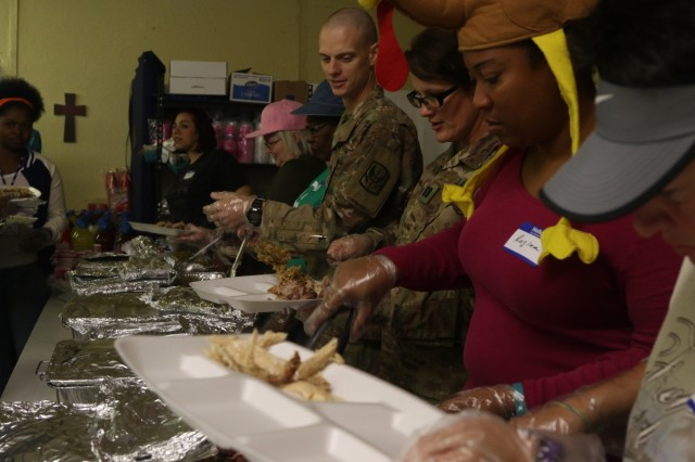 U.S. Army Capt. Jonathan Campbell and U.S. Army Capt. Katie Duffy, assigned to the 449th Combat Aviation Brigade, pile on Thanksgiving food to serve to patrons in need at the Jesus Hope and Love Mission church in Killeen, Texas on Nov. 23, 2017.  Soldiers stood side-by-side with the Jesus Hope and Love Mission staff and volunteers as they served Thanksgiving meals and donated their time feeding those in need.  (U.S. Army National Guard photo by Staff Sgt. Leticia Samuels, 449th Combat Aviation Brigade / Released)