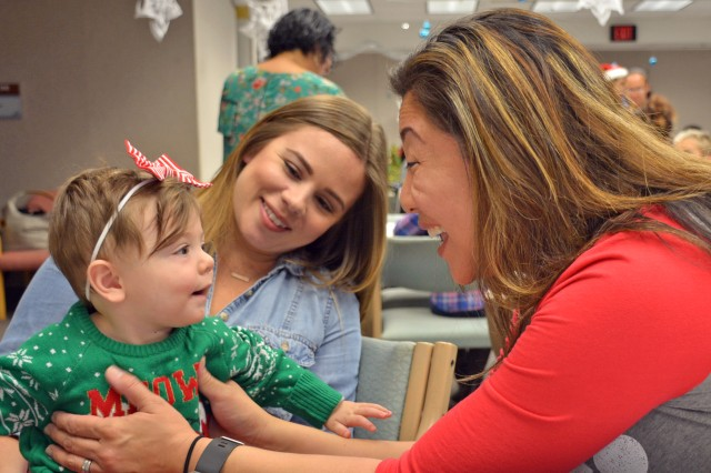 Tahney Meek and daughter Reagan Meek (left) reunite with Lynne Dela Cruz (right), a registered nurse at Tripler Army Medical Center's Neonatal Intensive Care Unit on December 3, 2017, during the eighth annual NICU Graduate Reunion.