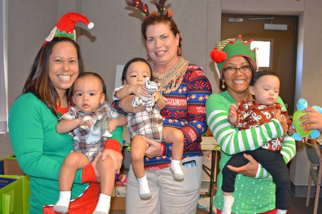 Registered nurses at the Tripler Army Medical Center Neonatal Intensive Care Unit Melinda Lote (left), Lorraine Ortega (center) and Mila French (right) reunite with the Lyons triplets during the eighth annual NICU Graduate Reunion on December 3, 2017.