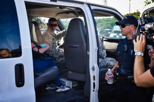 As Soldiers of the California National Guard's 140th Chemical Company drive, Ventura City Police Sgt, Kenny Welch assists residents load shuttles that will take them to their residence. For many residents impacted by the Thomas Fire, this was their first opportunity to witness first hand what, if anything, was left of their homes.