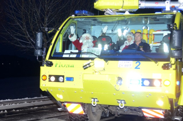 Santa and Mrs. Claus arrive with a little help from the Hohenfels Training Area's Fire Department on a snowy afternoon to assist with the Joint Multinational Readiness Center's Tree Lighting Ceremony Dec. 8, 2017. (U.S. Army photo by Staff Sgt. David Overson)