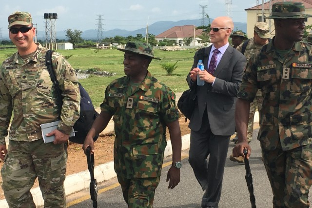 African Land Forces Summit 2018 lead planner, Lt. Col. Hector Montemayor (left) and Lt. Col. Husaini Toro, 176th Guards Battalion commander walk together at the proposed site for the summit's military demonstration in Abuja.  ALFS is a weeklong seminar designed to give African land force's chiefs an opportunity to discuss and develop solutions for improving security and stability in their home country.