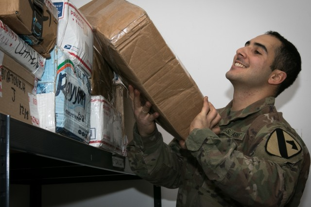 Private 1st Class Kaveh Amerfazli, a mailroom clerk and San Francisco native assigned to the 502nd Human Resources Company, 4th Sustainment Brigade, 1st Cavalry Division, pulls a package off the shelf for customers near Powidz, Poland Dec. 11, 2017. Atlantic Resolve is a U.S. endeavor to fulfill NATO commitments by rotating U.S.-based units throughout the European theater to deter aggression against NATO allies in Europe.