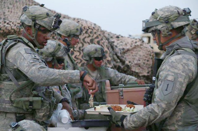 Soldiers from Golf Forward Support Company, 101st Brigade Support Battalion, 1st Armored Brigade Combat Team, 1st Infantry Division, serve a hot meal during National Training Center Rotation 16-08 in August 2016.