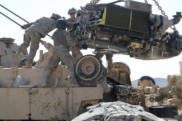 Crew members and mechanics from Golf Forward Support Company, 101st Brigade Support Battalion, 1st Armored Brigade Combat Team, 1st Infantry Division, reinstall an engine during National Training Center Rotation 16-08 in August 2016.