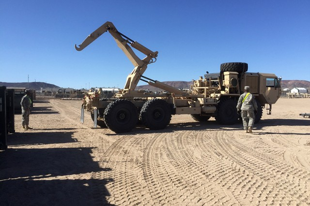 Soldiers prepare to load an M105 load handling system (LHS) compatible water tank rack onto an M1120 LHS during a 2017 National Training Center rotation at Fort Irwin, Calif.