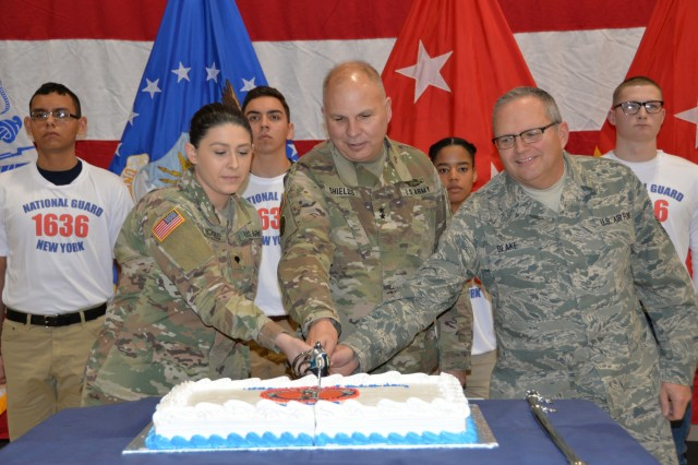 Maj. Gen. Raymond Shields, commander of the New York Army National Guard (middle) joins Air National Guard Chief Master Sgt. Michael Blake, age 58 the oldest  National Guard members present (right) and Army National Guard Spec. Jade Richards, age 19, one of the youngest members of the New York National Guard in cutting a cake in celebration of the National Guard's 381st birthday at New York National Guard headquarters  in Latham, N.Y. on December, 13 2017. The National Guard was established in 1636 and is the oldest military force in the Department of Defense.