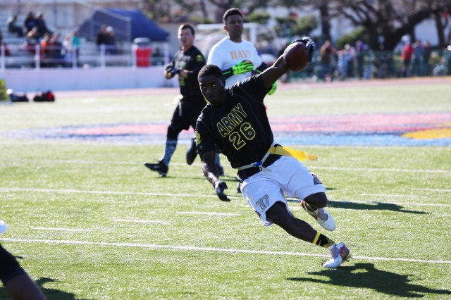 Staff Sgt. Talley Phillip, Team Army player, prepares to dodge Team Navy's defense during the annual Army vs. Navy flag football game Dec. 9 at Naval Air Facility Atsugi's Reid Memorial Stadium. U.S Army photo by Noriko Kudo)