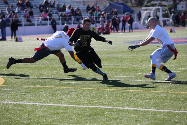 Sgt. 1st Class Gregory Hanneman, Team Army player, dodges Team Navy's defense during the annual Army vs. Navy flag football game Dec. 9, 2017 at Naval Air Facility Atsugi's Reid Memorial Stadium. (U.S. Army photo by Noriko Kudo)