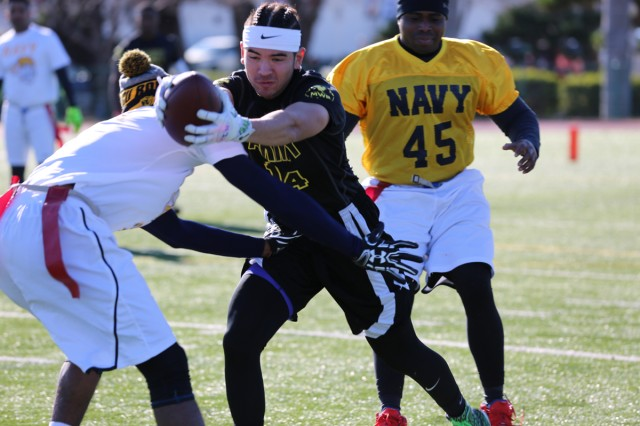 Anthony Ames, Family member on Team Army, protects the ball from Team Navy's defense during the annual Army vs. Navy flag football game Dec. 9, 2017 at Naval Air Facility Atsugi's Reid Memorial Stadium. U.S Army photo by Noriko Kudo)