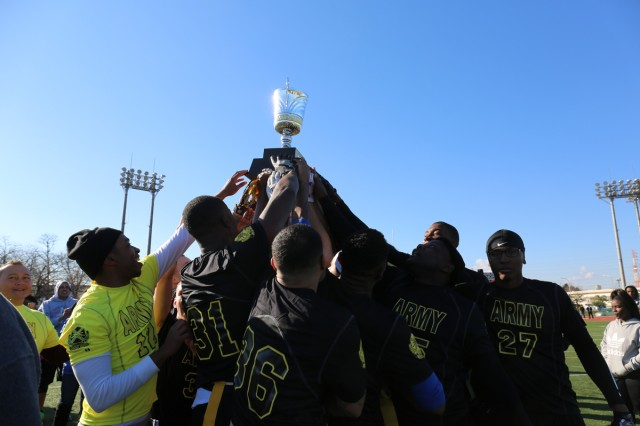 Camp Zama players formed a circle on the field to raise the trophy and celebrate its victory as Team Army after the annual Army vs. Navy flag football game Dec. 9, 2017 at Naval Air Facility Atsugi's Reid Memorial Stadium. U.S Army photo by Noriko Kudo)