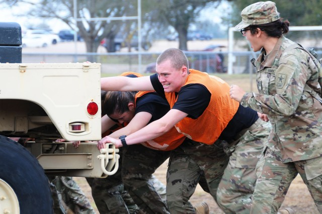 Pvt. Jacob Bolling, takes the edge position as he works with his team to push through the Humvee push challenge of the A Co., 1-13th Avn. Regt. Warrior Challenge Dec. 2.