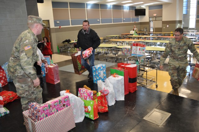 ACC employees line up the presents before the students arrive according to classroom for easy distribution.