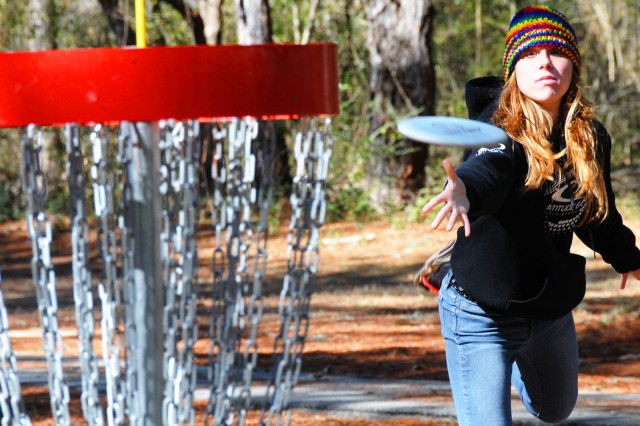 Stephanie Woodard, civilian participant and advanced female winner, tosses a disc at one of the baskets on the disc golf course during a previous Winter Fling Disc Golf Tournament at Beaver Lake.