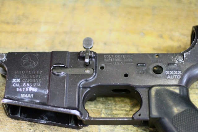 The receiver of a former M4 carbine shows laser etching to reflect it is now an M4A1 (left), and that it can fire full auto (right).