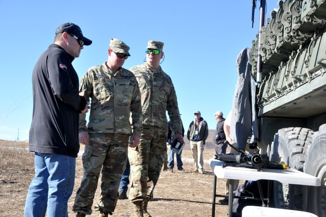 Robert Menti (left) , the senior manager for business development for Orbital ATK armament services division, talks with Maj. Gen. Wilson Shoffner (center), the commanding general of the Fires Center of Excellence and Fort Sill, and Brig. Gen. David Komar, director of the Capabilities Developments Directorate at the Army Capabilities Integration Center about the AUDS (anti-unmanned aerial vehicle defense system) during the  Maneuver Fires Integrated Experiment, Dec. 11 at Fort Sill. (Photo by Monica K. Guthrie)