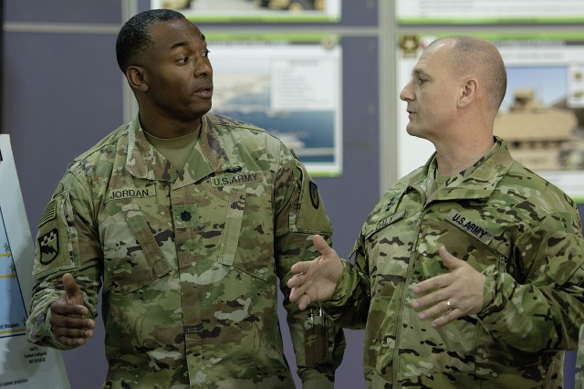 Lt. Gen. Edward Daly (right), deputy commanding general, U.S. Army Materiel Command speaks with Lt. Col. Mike Jordan, commander, Army Field Support Battalion-Kuwait during a tour of an Army Prepositioned Stocks-5 warehouse at Camp Arifjan, Kuwait, Dec. 9. (U.S. Army Photo by Justin Graff, 401st AFSB Public Affairs)