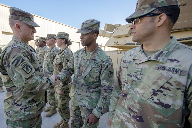 Lt. Gen. Edward Daly, deputy commanding general, U.S. Army Materiel Command awards coins to Army Field Support Battalion-Kuwait personnel during a tour of an Army Prepositioned Stocks-5 warehouse at Camp Arifjan, Kuwait, Dec. 9. (U.S. Army Photo by Justin Graff, 401st AFSB Public Affairs)